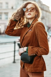 Fashionable woman wearing leopard print sunglasses, brown corduroy blazer, trousers, black leather belt bag, silver bracelet, posing in street of european city