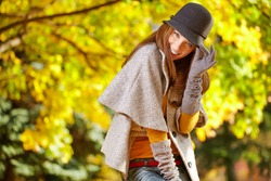 Fashionable woman with autumn leaves in hand and fall yellow maple garden background