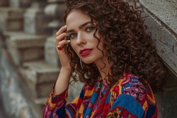 Fashionable woman with long curly hair, red lips makeup, wearing trendy summer colorful printed shirt, stylish ring with big gem, posing in city. Copy, empty space for text