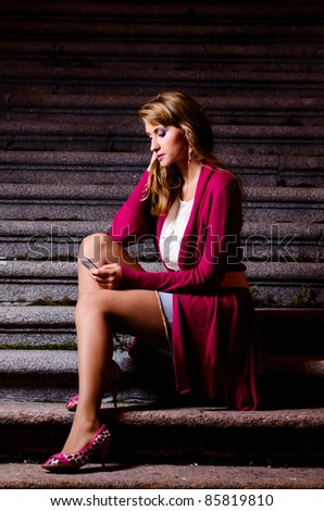 fashionable woman with mobile phone in hands is sitting on stairs at evening