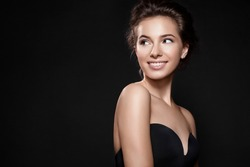 Fashionable woman with perfect smile and clean skin on black background