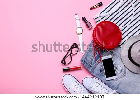 Fashionable women's clothes with cosmetics and accessories on pink background