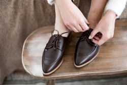 fashionable women's shoes, feet in the interior, classic women's flat shoes, brown leather shoes, mules and loafers, knitted blankets and blankets on the background, wooden background, cotton flowers,