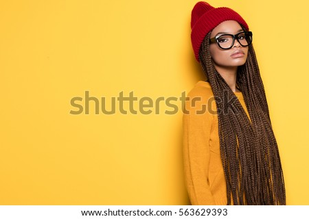 Fashionable young african american girl wearing red cap posing on yellow background. #563629393