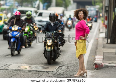 Fashionable young asian woman stands near a busy city highway. - Shutterstock ID 397892260