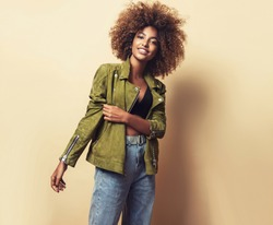 Fashionable young beautiful african american woman . Girl with afro hairstyle posing in leather jacket. Fashion, clothing and style.