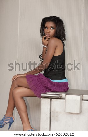 Fashionable young black woman sitting