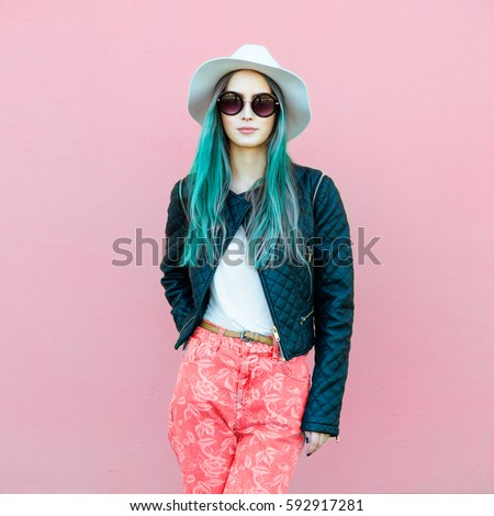 Fashionable young blogger woman with blue hair wearing casual style outfit with black jacket, white hat, pink jeans and sunglasses posing near the wall.