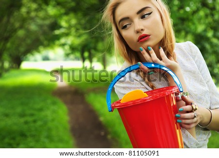 Fashionable young blonde poses in park avenue with a red bucket.