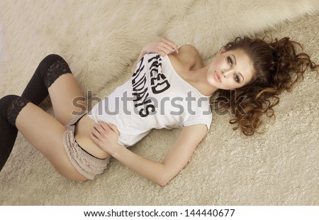 Fashionable young brunette sensual woman lying on fur, looking at camera.