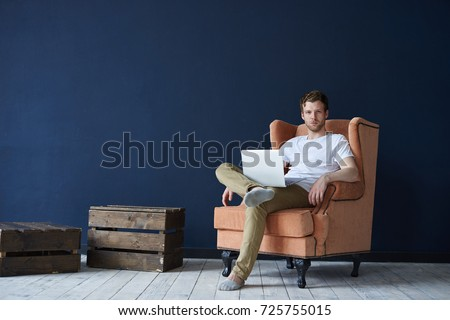 Fashionable young Caucasian man with beard relaxing in modern loft space interior, sitting on orange armchair and surfing internet on laptop pc. Handsome guy enjoying online communication using gadget