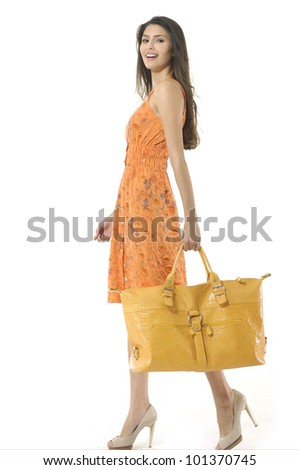 Fashionable young girl with a handbag walking on white background