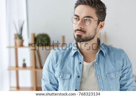 Fashionable young male worker or manager wears spectacles, stylish denim shirt, has thoughtful expression, looks with clever look aside, stands over home or office interior. Facial expressions concept #768323134
