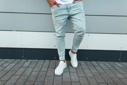 Fashionable young man in a t-shirt in trendy ripped blue jeans in stylish white leather sneakers stands on the street near the wall. Modern guy in the city. Summer men's clothing. Close-up.