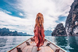 fashionable young model in boho style dress on boat at the lake