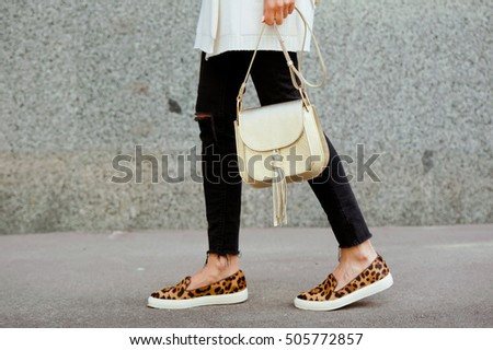 Fashionable young woman in black jeans, white cardigan and leopard shoes with gold handbag on the city streets. Fashion. Stylish .
