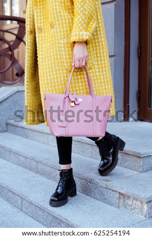 Fashionable young woman in yellow coat with rose handbag in hand . Street style . #625254194