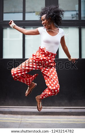 Fashionable young woman jumps up and laughs, full length
