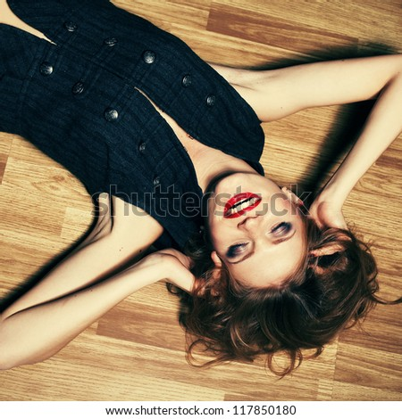 fashionable young woman lying on wooden floor and laughing. studio shot