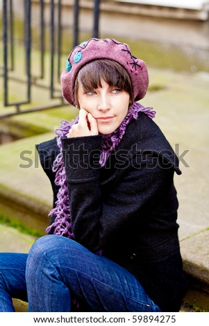 fashionable young woman wearing beret sitting on stairs and looking away