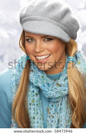 Fashionable Young Woman Wearing Cap And Knitwear In Studio