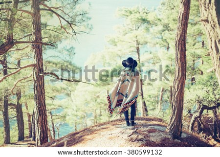 Fashionable young woman wearing in hat and poncho standing on coast in the forest among pine trees and looking at sea, rear view #380599132