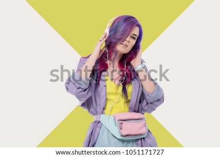fashionable young woman with colorful hair in purple trench coat listening music with headphones #1051171727