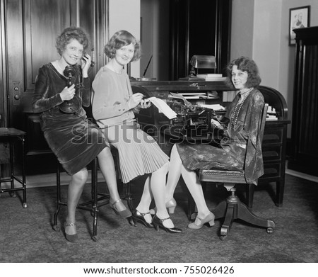 Fashionable young women in a Washington, D.C. office, May 1, 1929. One holds a telephone, another a stenographic pad, and the third sits at a typewriter.