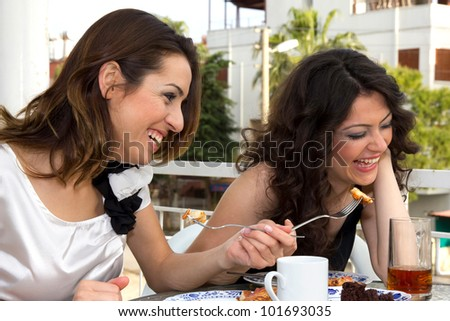Fashionable young women laughing and joking at a restaurant over a morsel of food that is being offered over the table on a fork