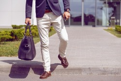 fashionably dressed businessman walks from office building with a bag and car keys in his hand.