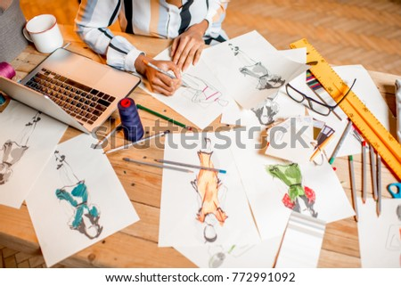 Fasion designer sketching clothes drawings at the table with tailoring tools and laptop #772991092