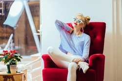 Fasionable hipster blonde woman in sunglasses relaxing in red retro armchair in modern store showroom.