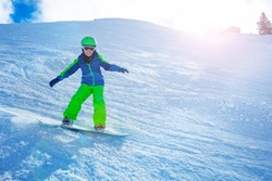 Fast action photo of a boy going downhill on snowboard view from side balancing with hands and snow powder sun backlit