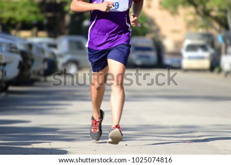 fast athlete runs down the street during the race outdoors #1025074816