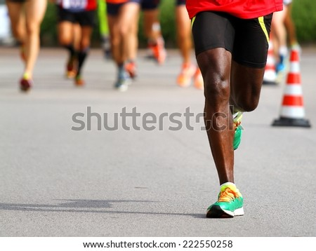 fast athlete runs down the street during the race outdoors #222550258