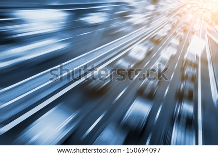 fast cars on freeway, sunlight in background