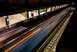 Fast driving metro train at night with light trails in Athens, Greece with a platform and railroad