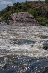 Fast flowing cold water mountain stream, flowing stormy stream stream, nature outdoors, fresh stream dark blue water.