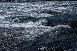 Fast flowing cold water mountain stream, flowing stormy stream stream, nature outdoors, fresh stream dark blue water, clean environment, waves and splashes close-up
