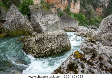 Fast flowing water of the Tarn river round huge boulders in the Gorges du Tarn Averyron France