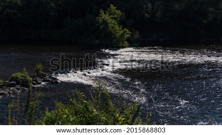 Fast flowing water on River Ave in Vila do Conde, Portugal. Bright sunny day in summer. Foto stock ©