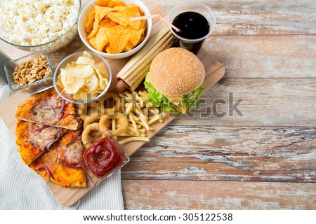 fast food and unhealthy eating concept - close up of fast food snacks and cola drink on wooden table Stock photo ©