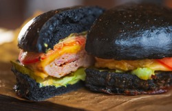 Fast food delivery.Big black burger cut into halves.Delicious beef meat with vegetables,cheese and sauce in crusty buns from dark dough.Tasty American fastfood in restaurant order from take away menu