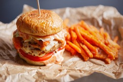 Fast food delivery.Delivered cheeseburger & carrot fries on brown paper.Delicious fastfood take away menu in close up.American fastfood restaurant takeaway dishes,order to deliver on carantine