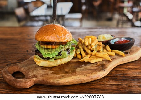 Fast food dish. Appetizing meat burgers, potato chips and vegetable. Takeaway composition. French fries, hamburger and sauces on wooden board with copy space.