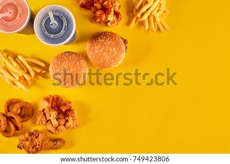 Fast food dish on yellow background. Fast food set fried chicken, meat burger and french fries. Take away fast food. #749423806
