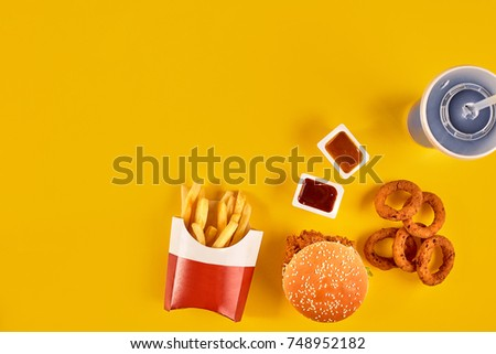 Fast food dish top view. Meat burger, potato chips and wedges. Take away composition. French fries, hamburger, mayonnaise and ketchup sauces on yellow background. #748952182