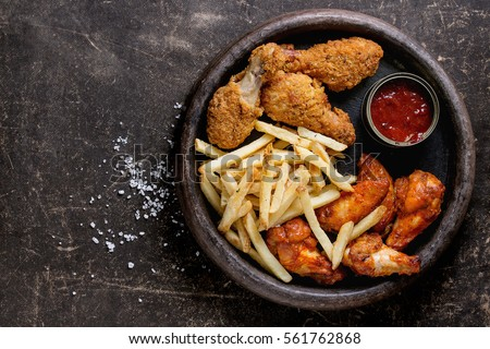 Shutterstock Fast food fried crispy and spicy chicken legs, wings and french fries potatoes with salt and ketchup sauce served in stone plate over dark texture background. Top view, space for text