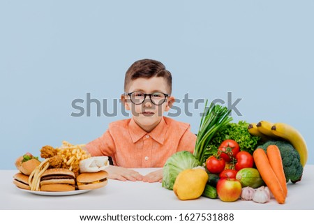 fast food. little boy with eyeglasses. healthy foods and unhealthy foods, isolated on blue background. studio Imagine de stoc ©