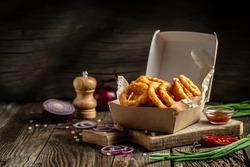 fast food meal onion rings in paper box on wooden table. American food concept. banner, menu, recipe, place for text.